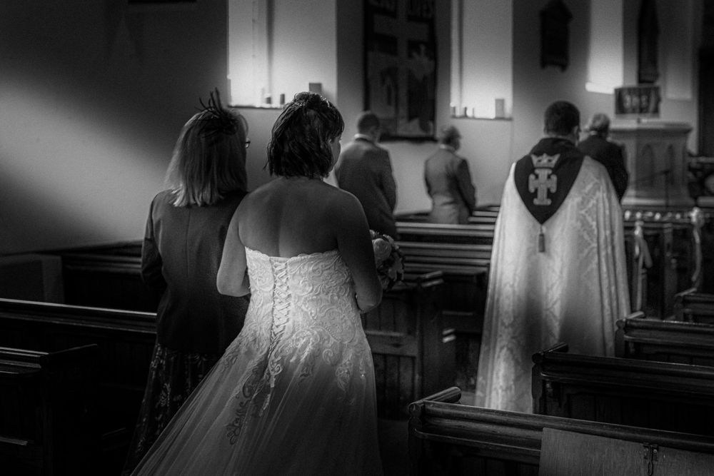 Black and white photo of bride walking up the isle in Manchester