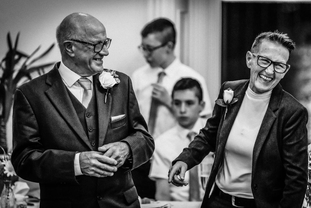 Black and white photo of guests laughing during reception