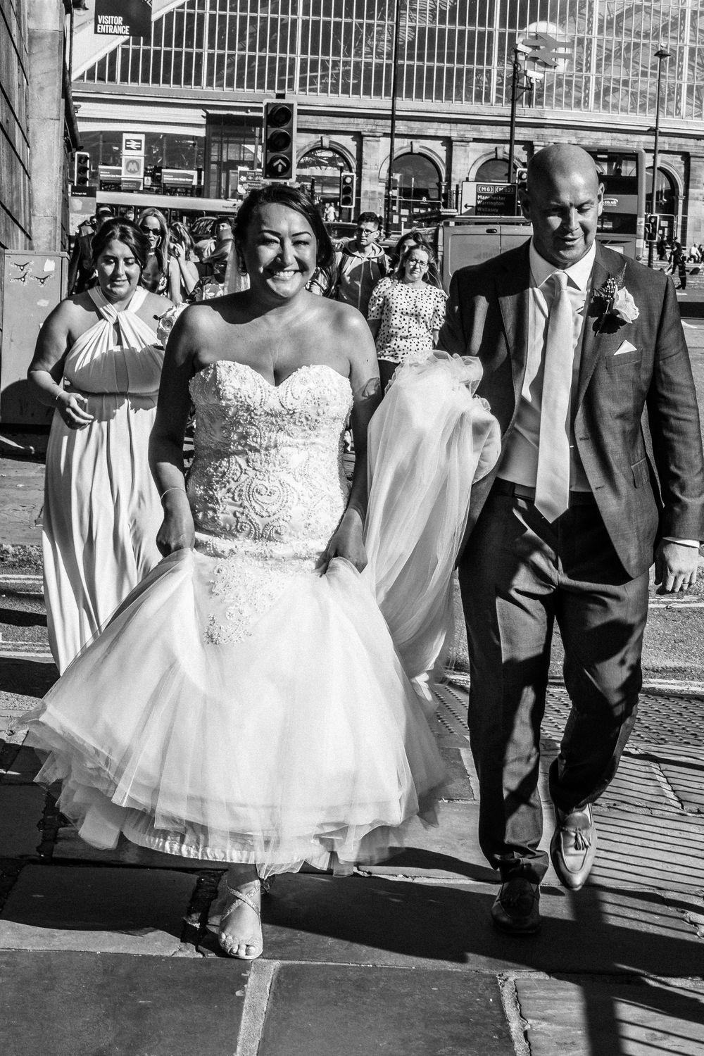 Black and white photo of bride and groom walking in Liverpool