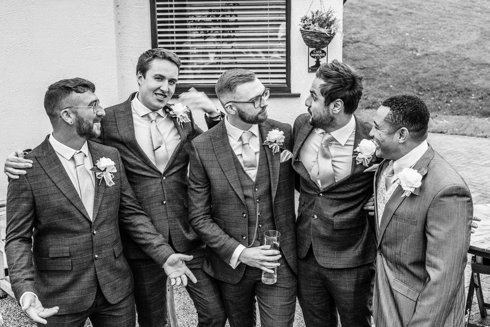 Black and white photo of groom and groomsmen at wedding in Wales