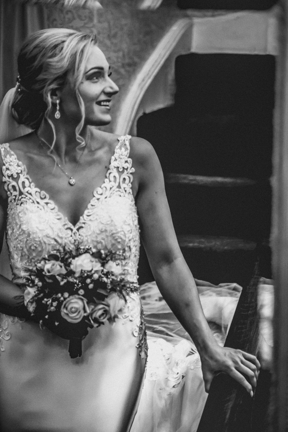 Black and white photo of Bride walking down stairs, reflected in mirror