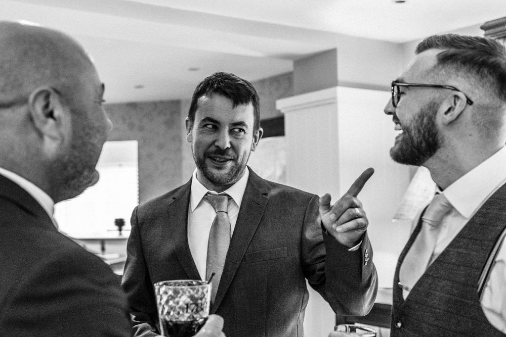 Black and white photo of groom laughing with guests