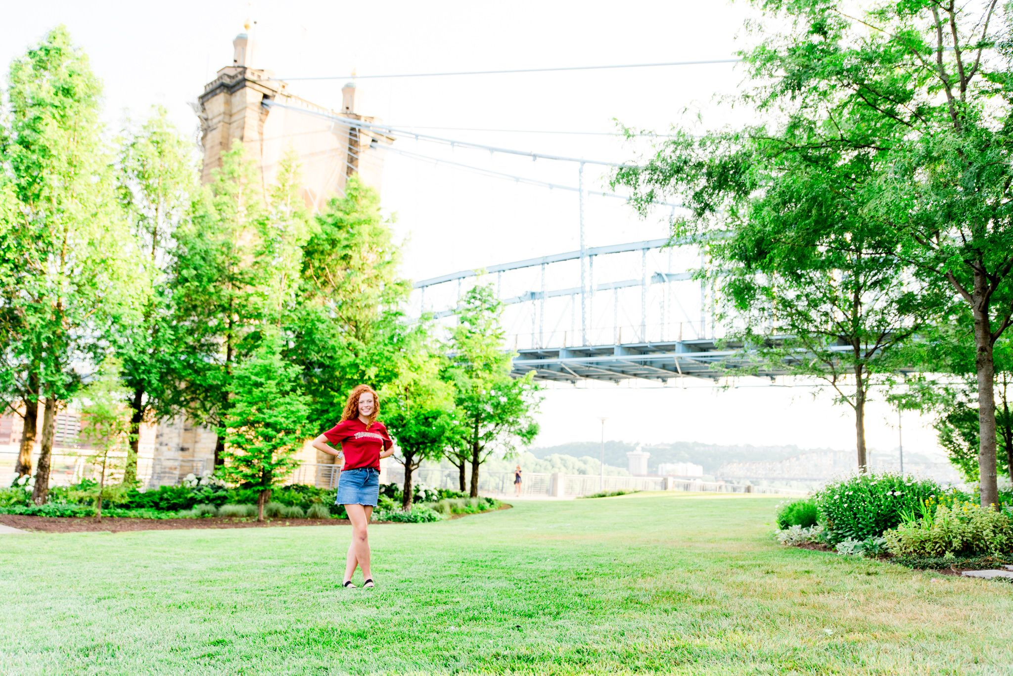 young woman in red Transylvania shirt standing in Smale Park in front of the Roebling Bridge