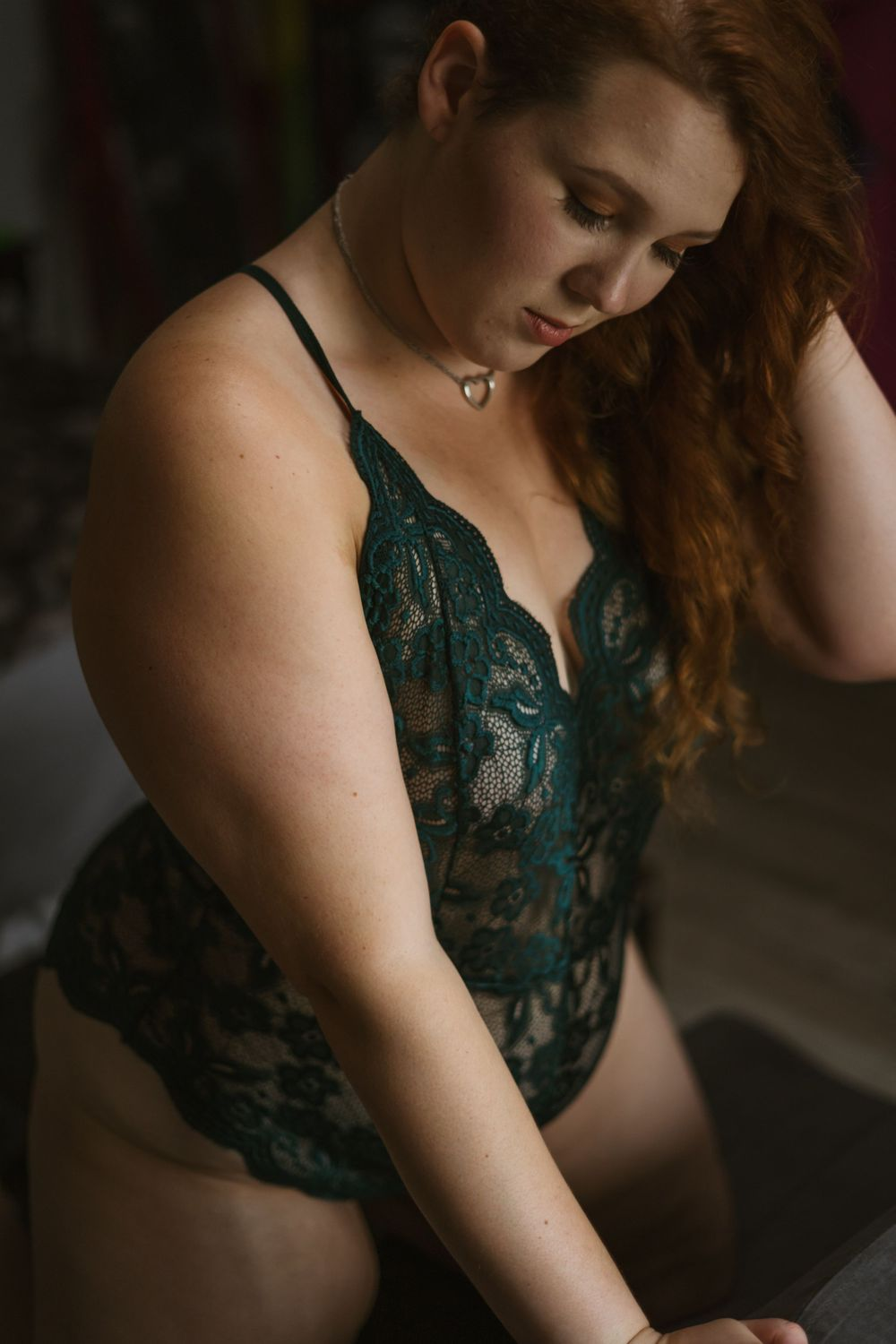 plus size woman with red hair and light skin looks down at the couch she is kneeling on. She is wearing a green bodysuit
