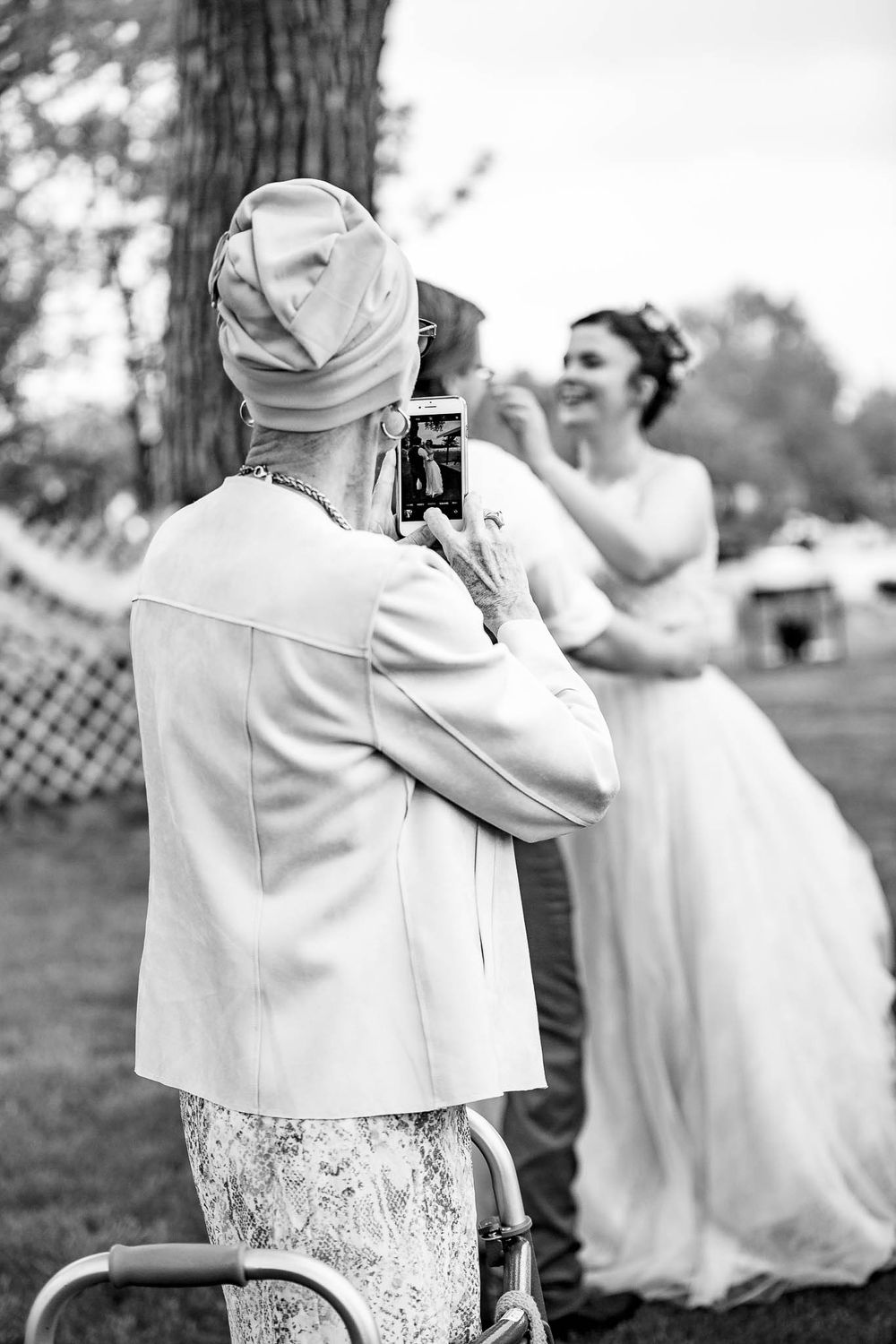 Wedding documentary photography of grandma taking a photo with her cell phone