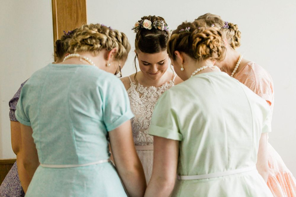 Bridesmaids pray with the bride before her wedding at Camp Nebowa