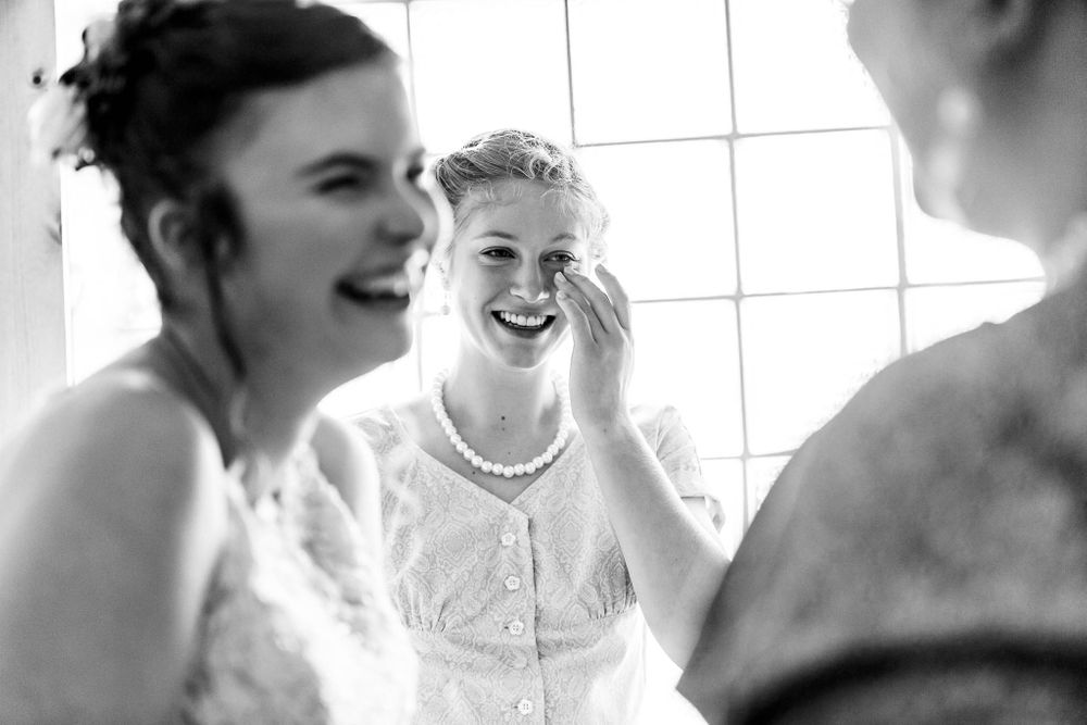 A bridesmaid wipes away tears of joy as she laughs with the bride.