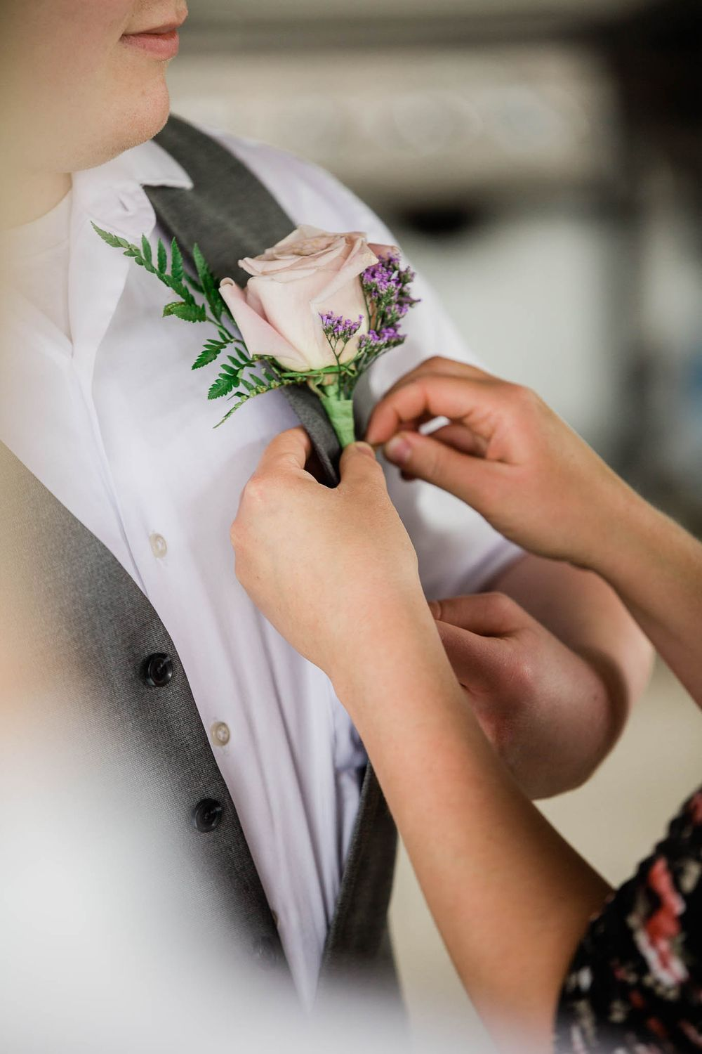 A groom has his boutonniere pinned onto his vest.