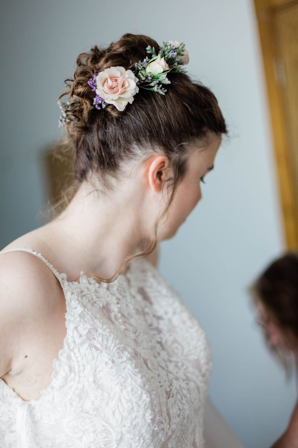 A bride wearing spring flowers in her hair and preparing for her wedding.
