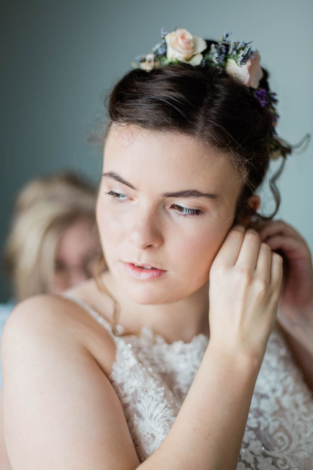 Iowa bride putting her earrings in while looking out the window.