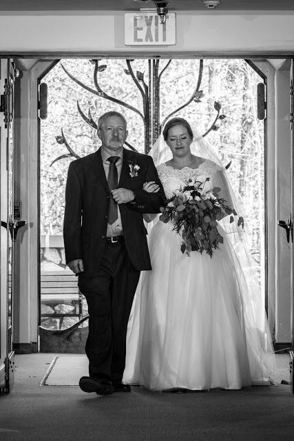 Father walking the bride down the isle black and white