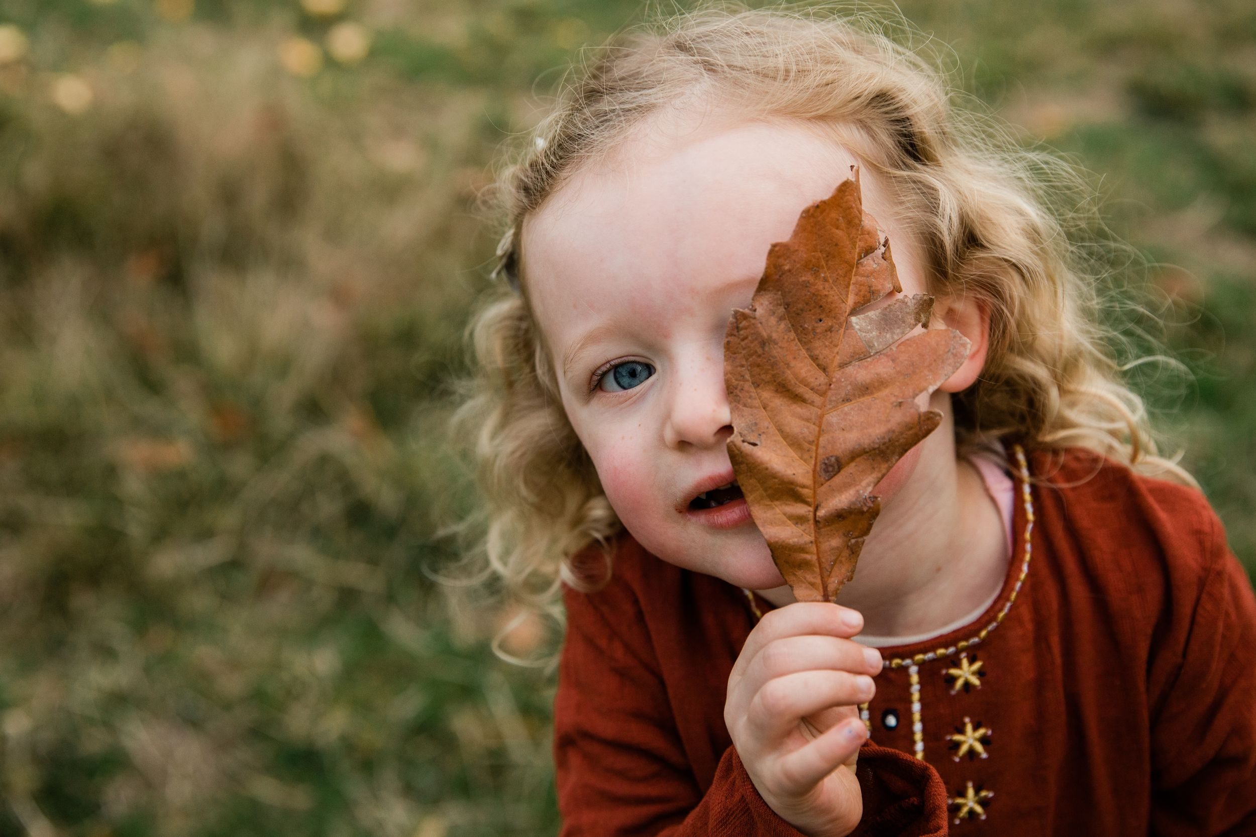 toddler holding an autumn leaf