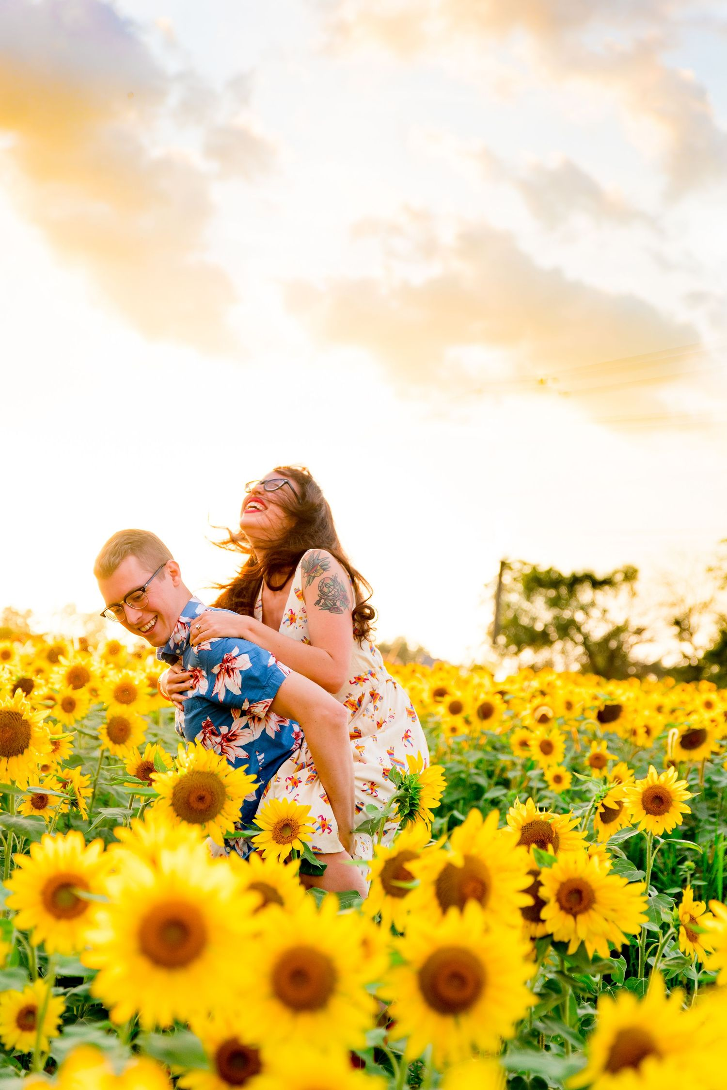laughing engaged couple doing a piggyback ride in a sunflower field at sunset in Chicago