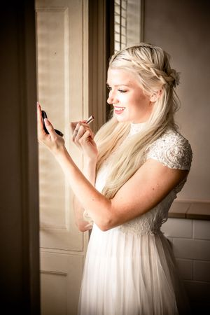 Bride putting on make up at a country house wedding in Kent