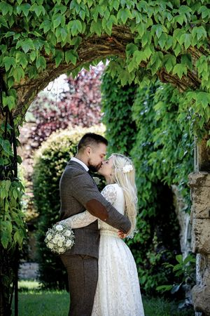 Bride and Groom kissing under an arch