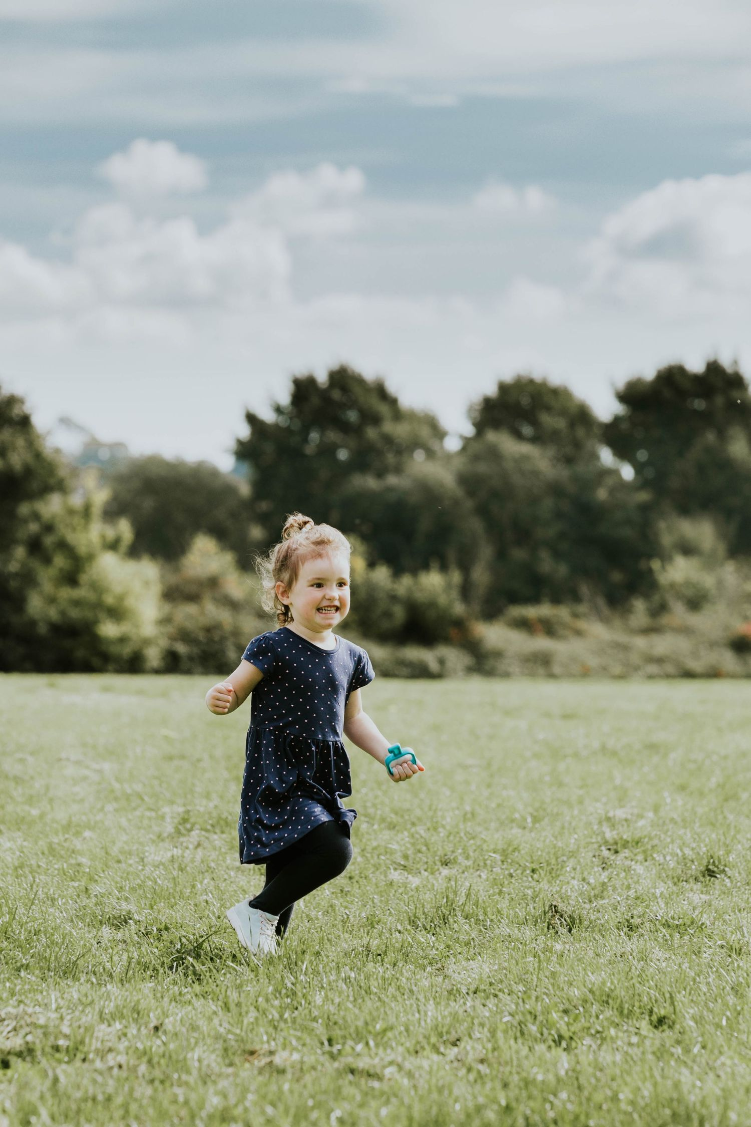 little girl running through field