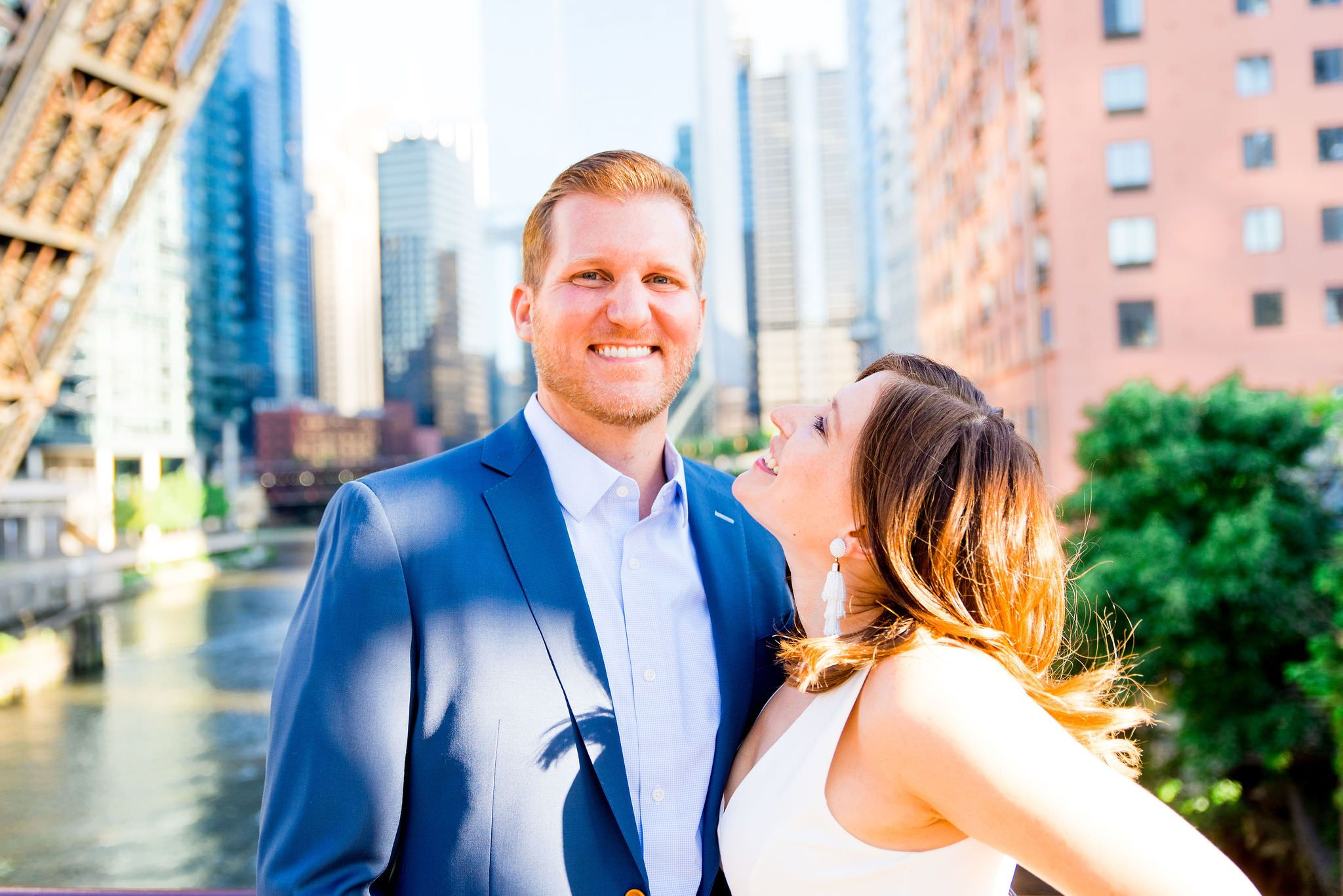woman in white dress smiling at man in navy suit in front of Chicago River at Kinzie St Bridge engagement pictures