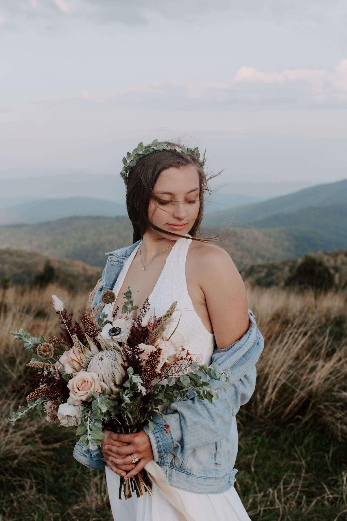North Carolina elopement bride on top of a mountain with the wind blowing through her hair. Audrey Darke Photography