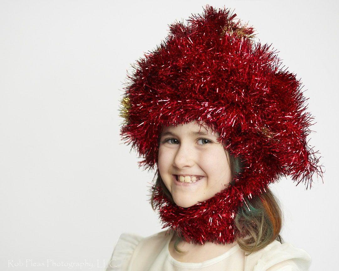 portrait of girl wearing headdress made of red garland from the Christmas tree