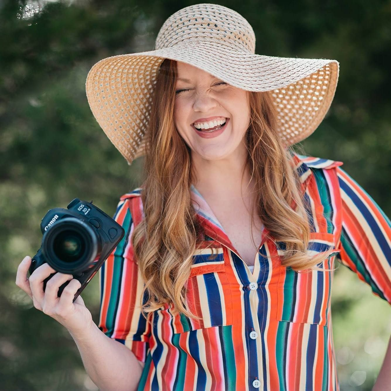 Female photographer, holding camera, floppy hat, stripe dress