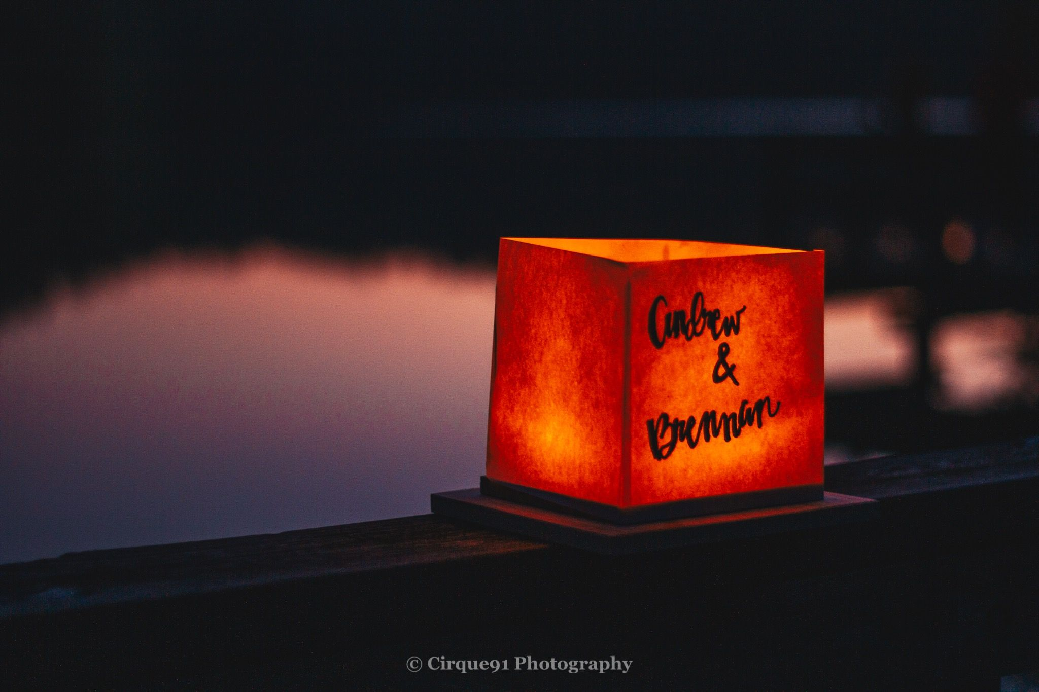 water lantern with words Andrew & Brennan written during sunset with lake reidsville in the background