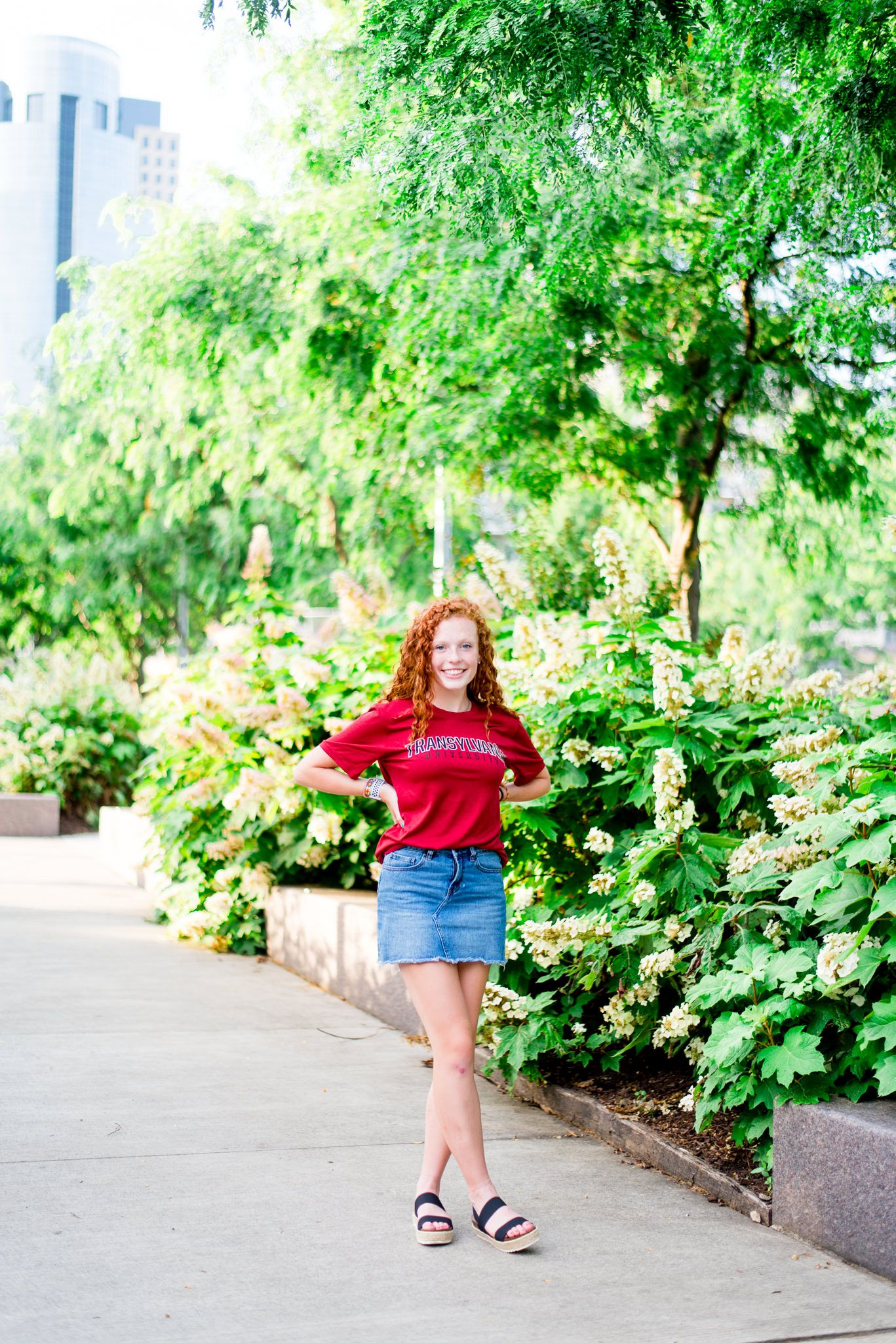 young woman with red curly hair in red Transylvania shirt and denim skirt walking through Smale Park hydrangeas