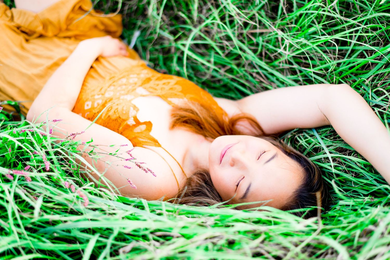 young woman in yellow lace dress laying in green grass with eyes closed