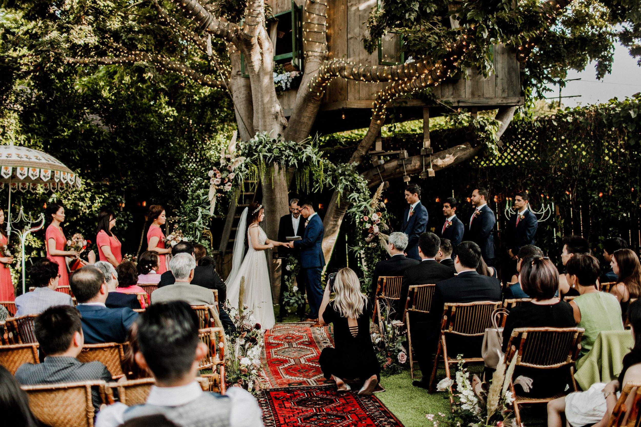 portrait behind the scenes of videography at wedding ceremony with treehouse background