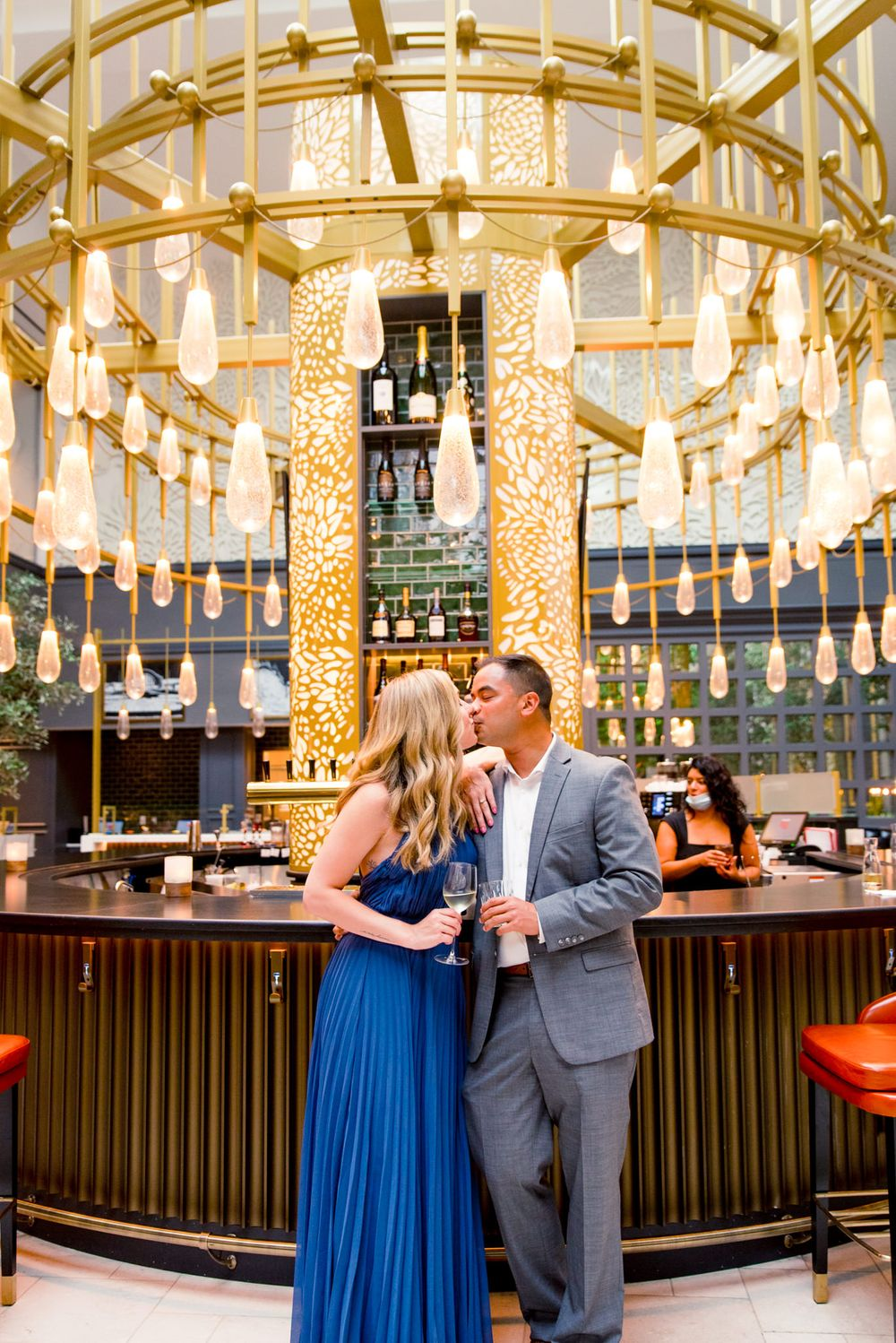 young engaged couple in blue and grey kissing in front of gold chandelier at Lytle Park Hotel bar
