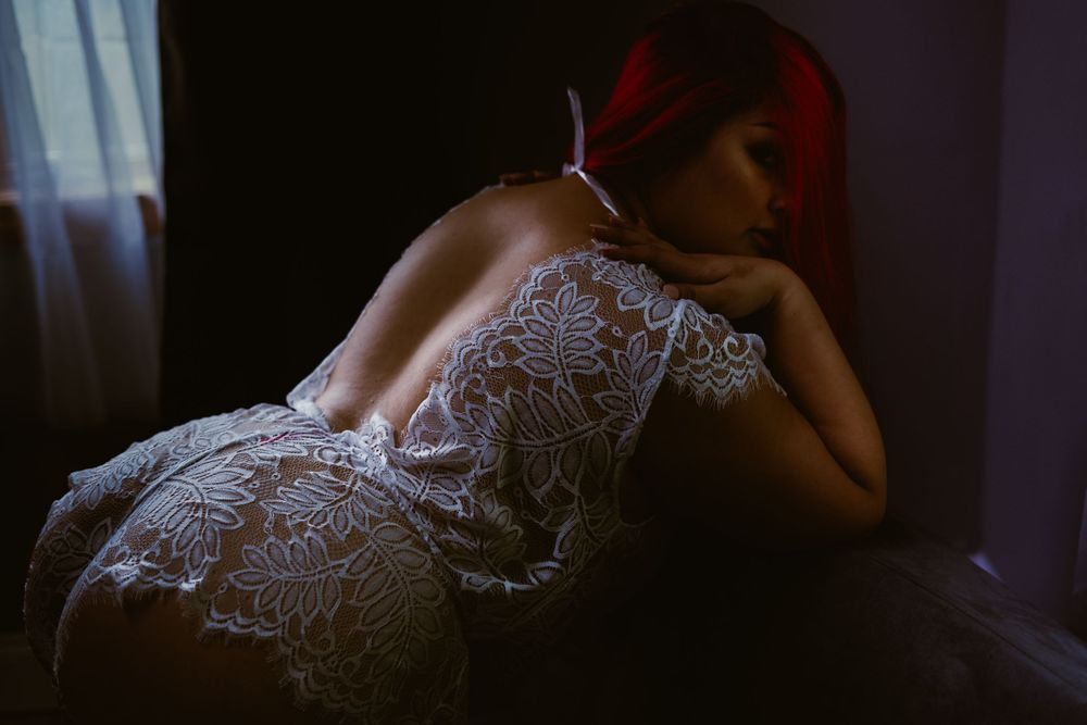 woman in white lingerie with open back touches her shoulders and looks through her hair