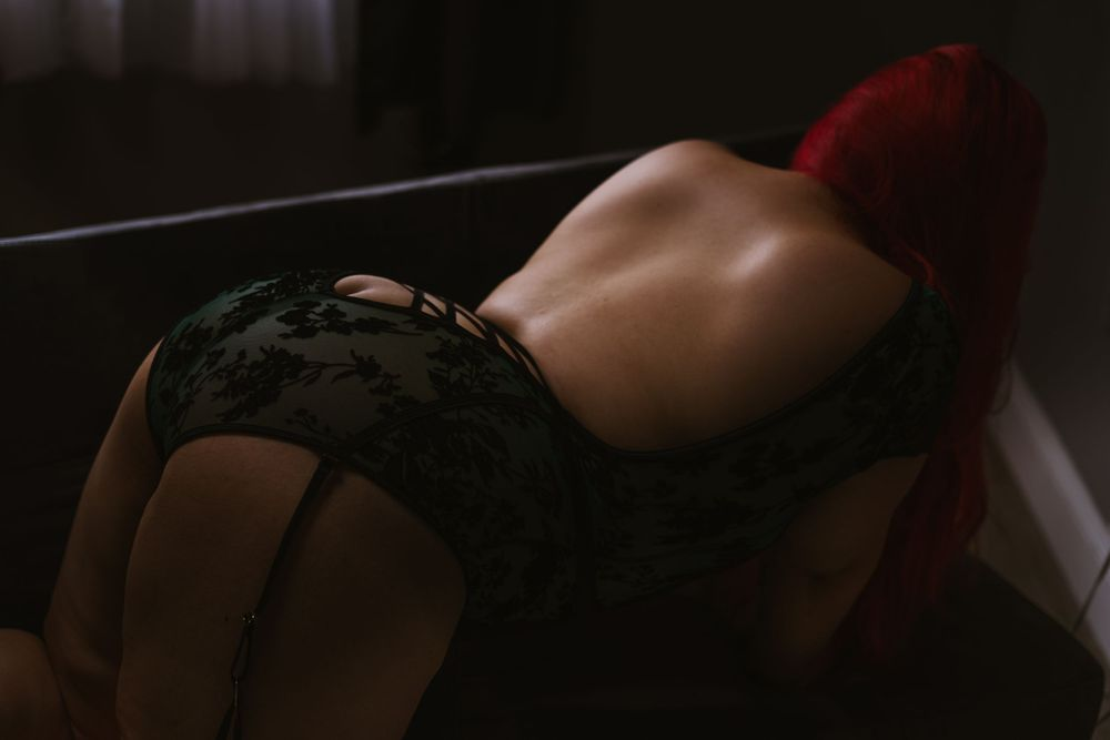 dark and moody boudoir image of a woman on all fours on a couch, shows off the lines of her back and shoulderblades