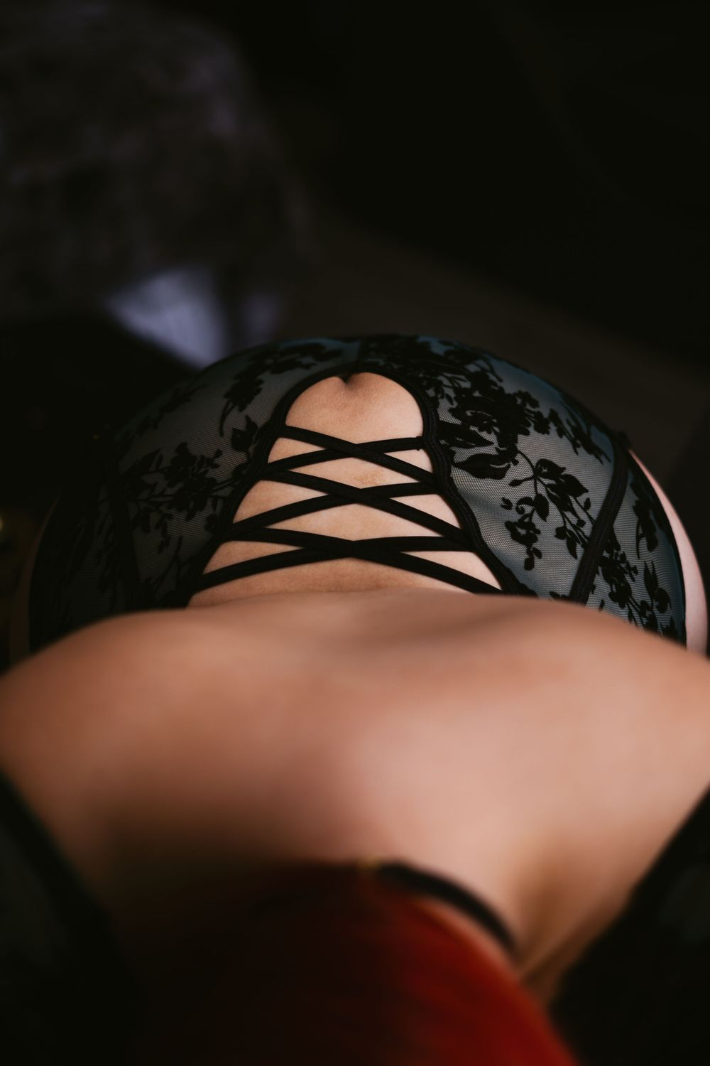 back of a woman looking down from her head, showing off her curves and the strappy green lingerie over her lower back