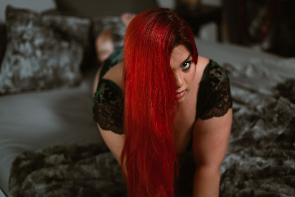 woman looking up through her red hair, confident and on a bed with grey fur texture