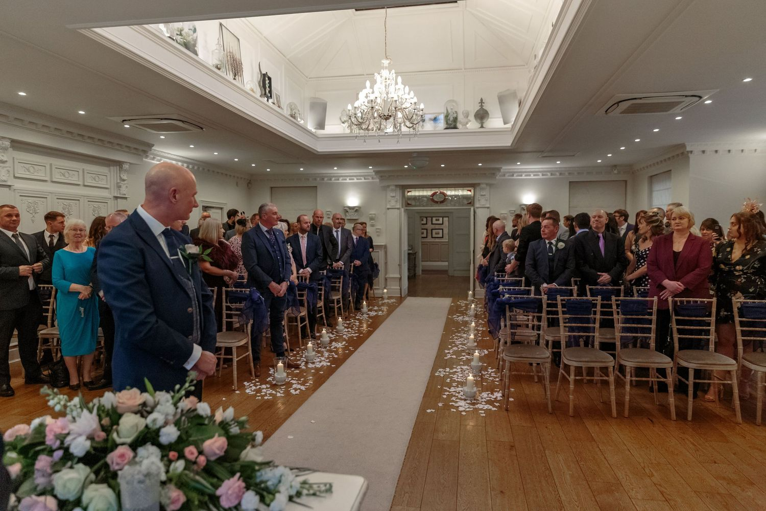 groom standing at the front of the room in front of the wedding guests turns to look for the bride
