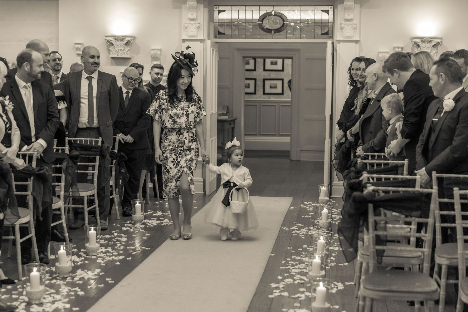 little flower girl walks up the aisle with her mother