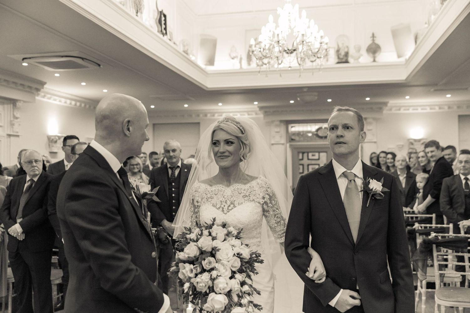 bride escorted by her brother reaches her groom after walking up the aisle