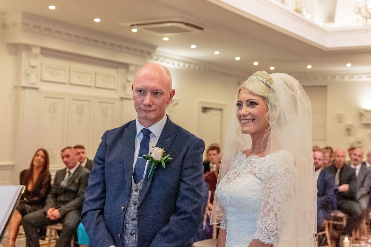 bride and groom smiling at the front of the room in front of all their guests