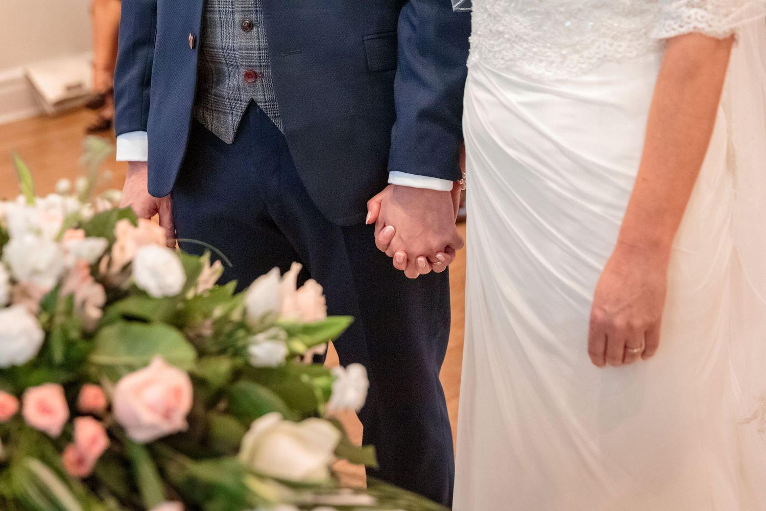 close up of the node and groom holding hands during the wedding ceremony