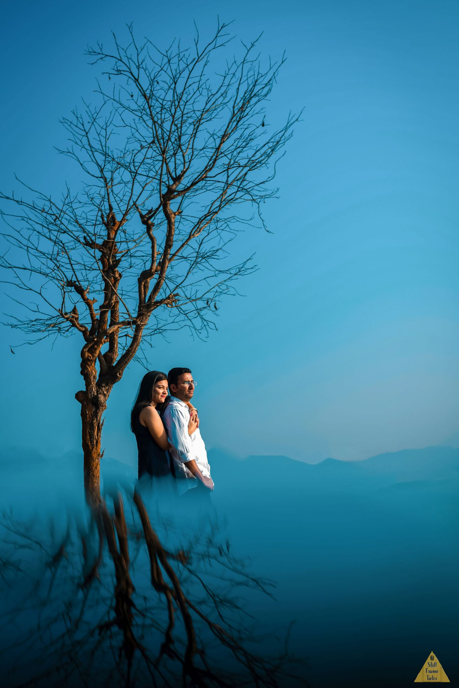 Couple cuddling in sun light beside tree with blue sky background reflection
