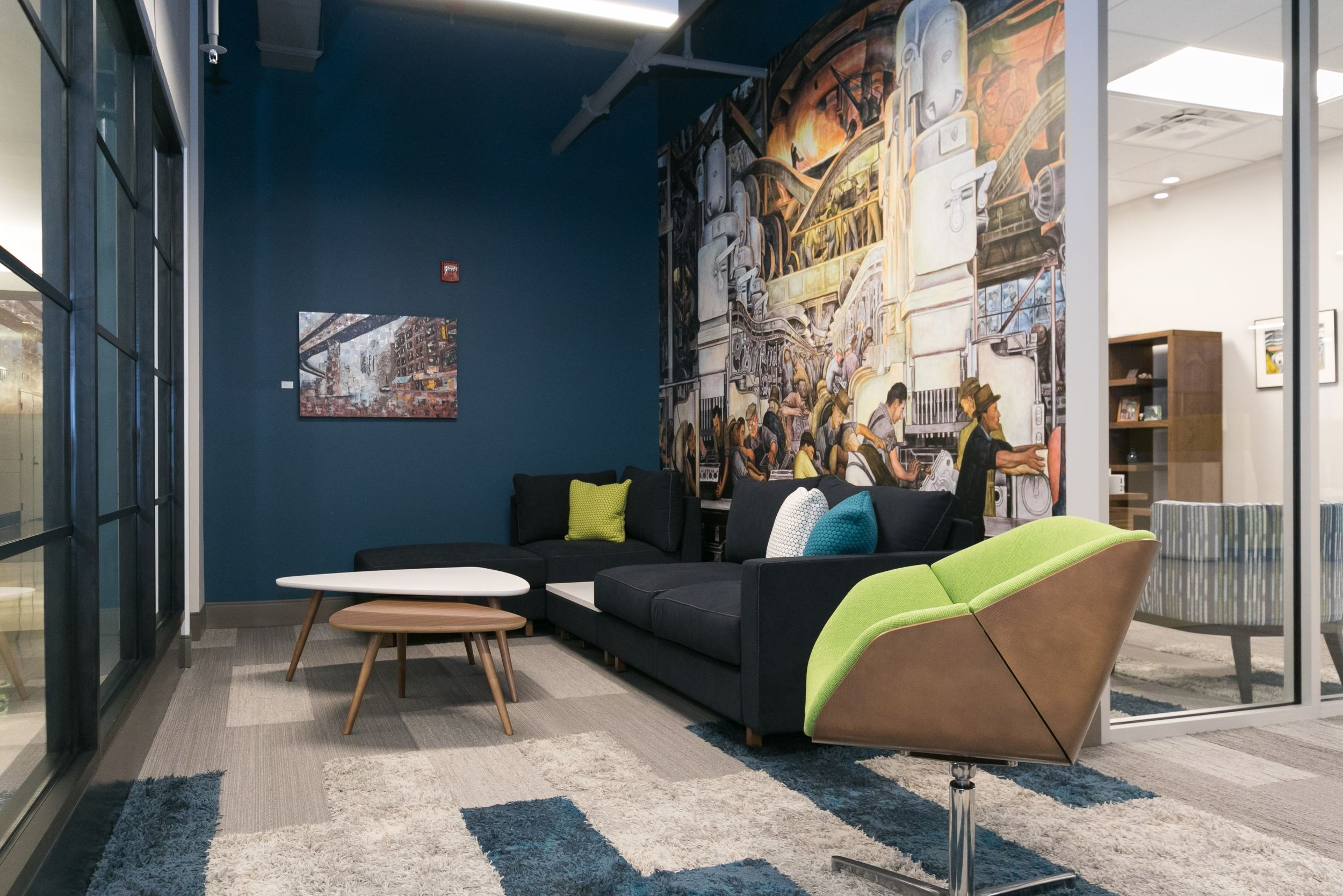 Blue, green, and gray lounge space amongst a Detroit mural at Burris Law firm.