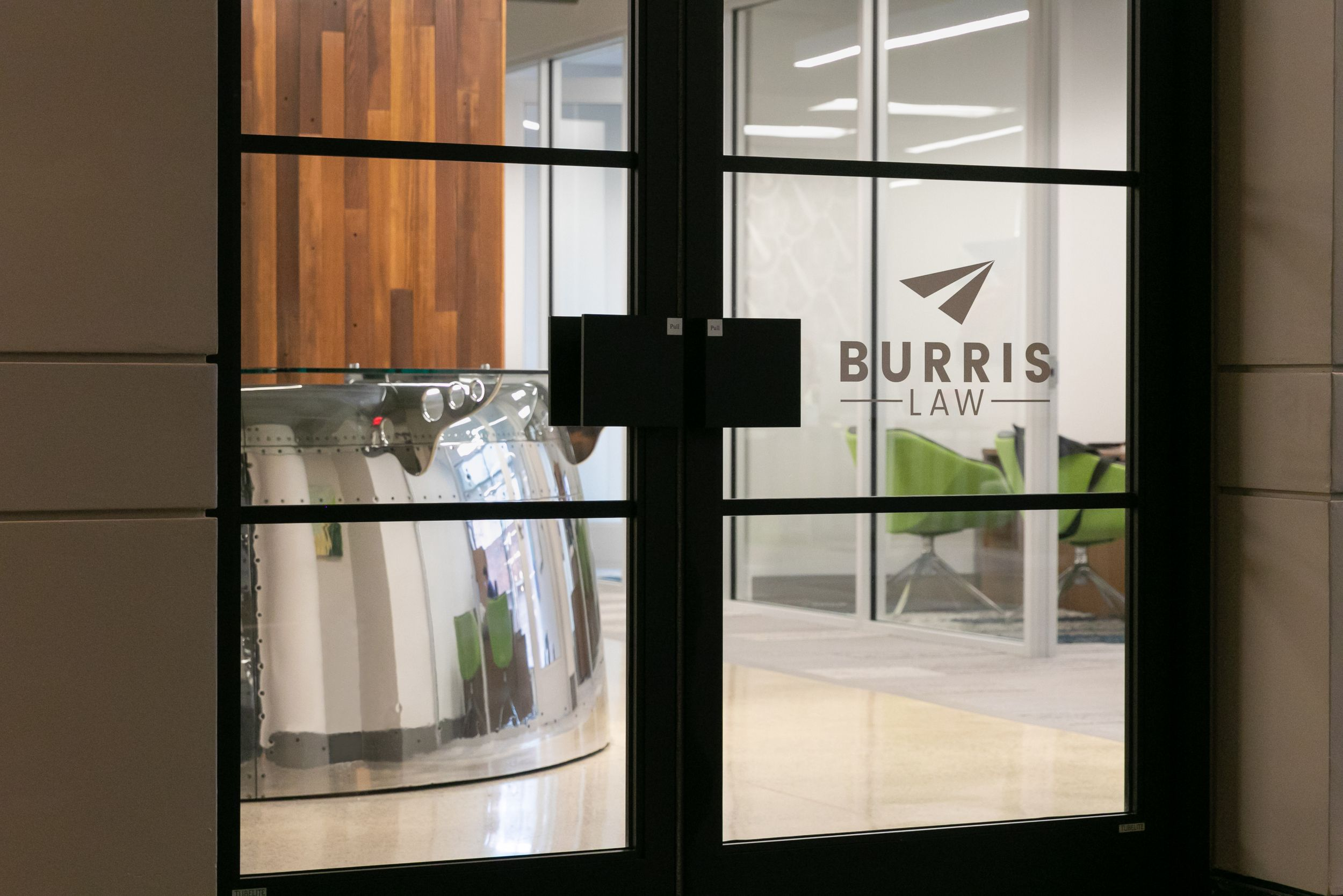 Close-up image of glass doors welcoming visitors into the space with the Burris law logo on the door.