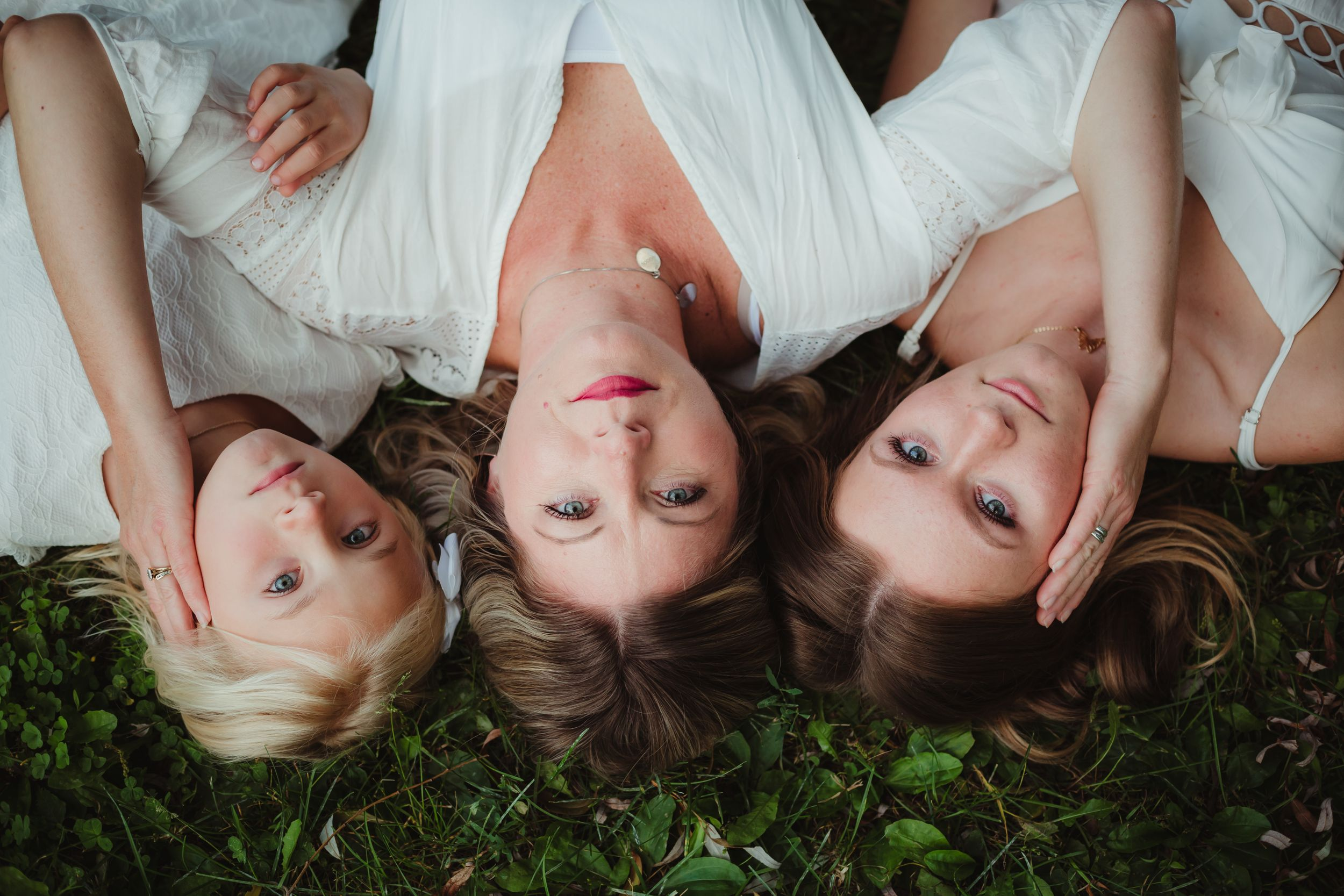 Mom and two daughters wearing white dresses lying on the ground looking seriously at the camera.