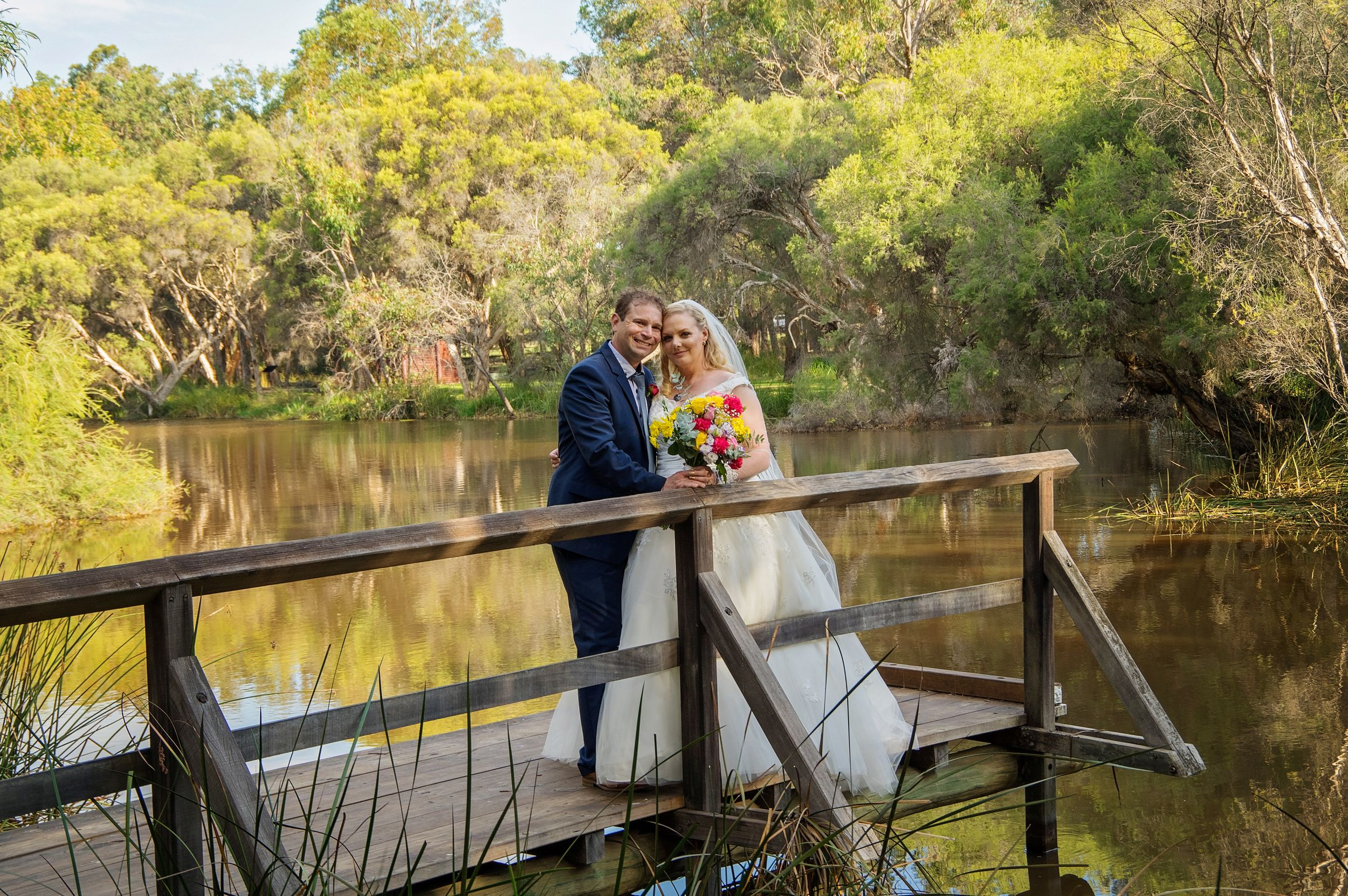 bride and groom posing on bridge at Whiteman park