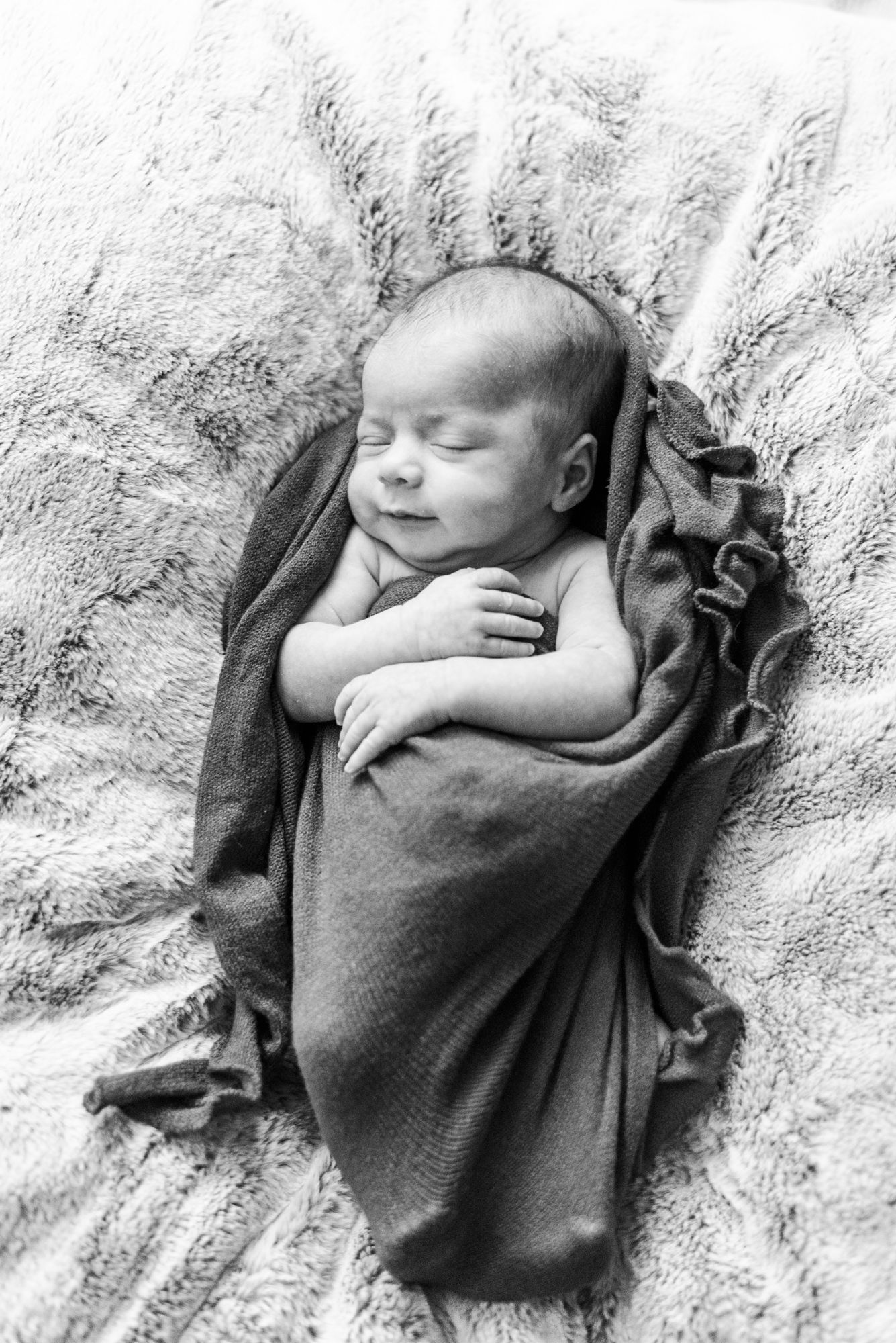 Lifestyle newborn baby laying in wrap smiling in black and white in Pittsburgh, Pennsylvania