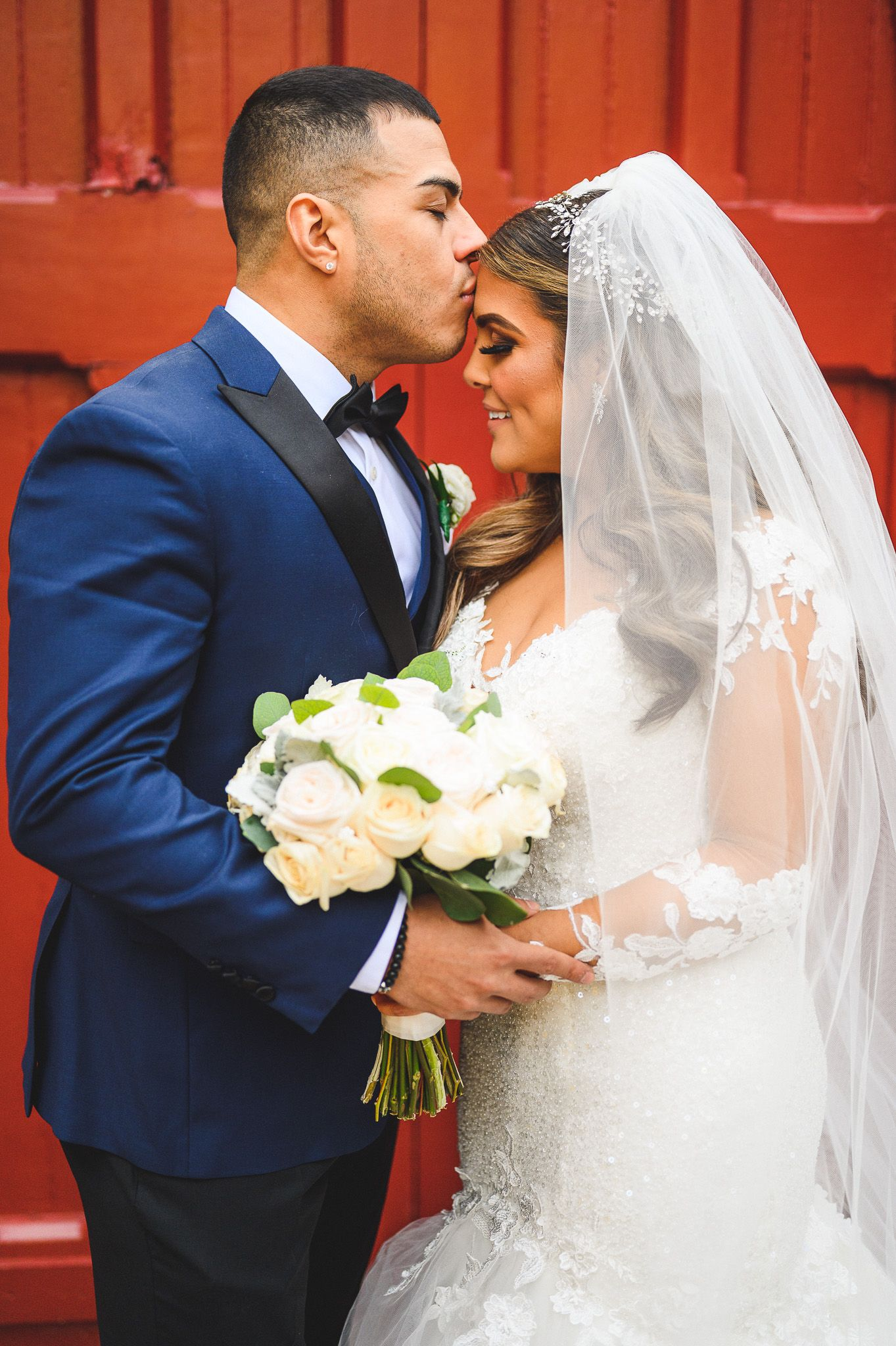 groom kissing his bride forehead in front of red doors at stone house