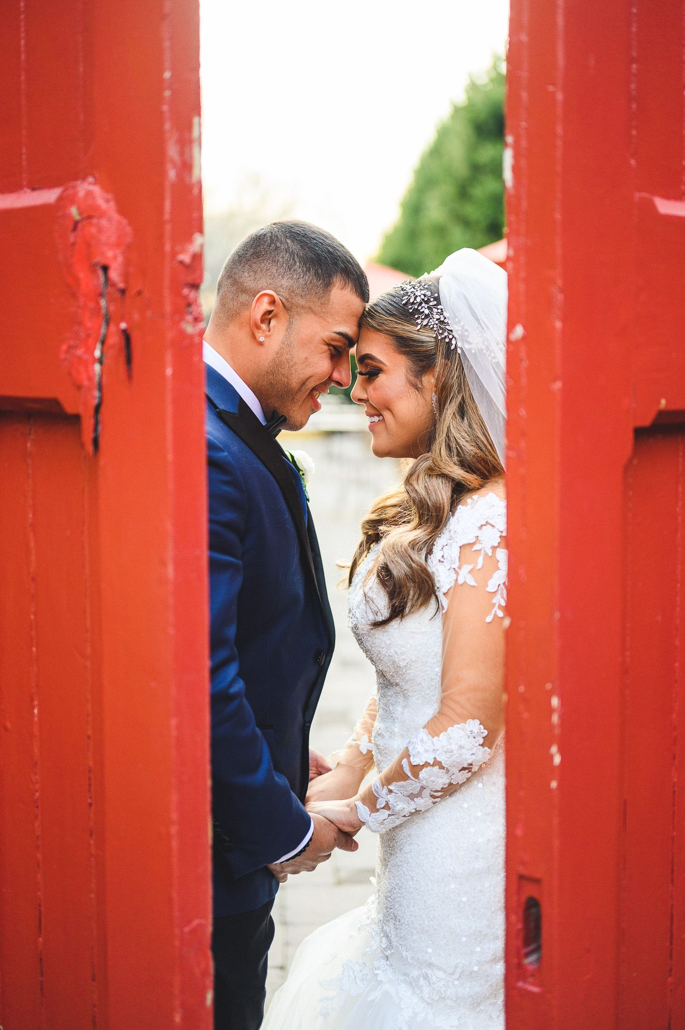 bride and groom smiling with foreheads together between red doors at stone house