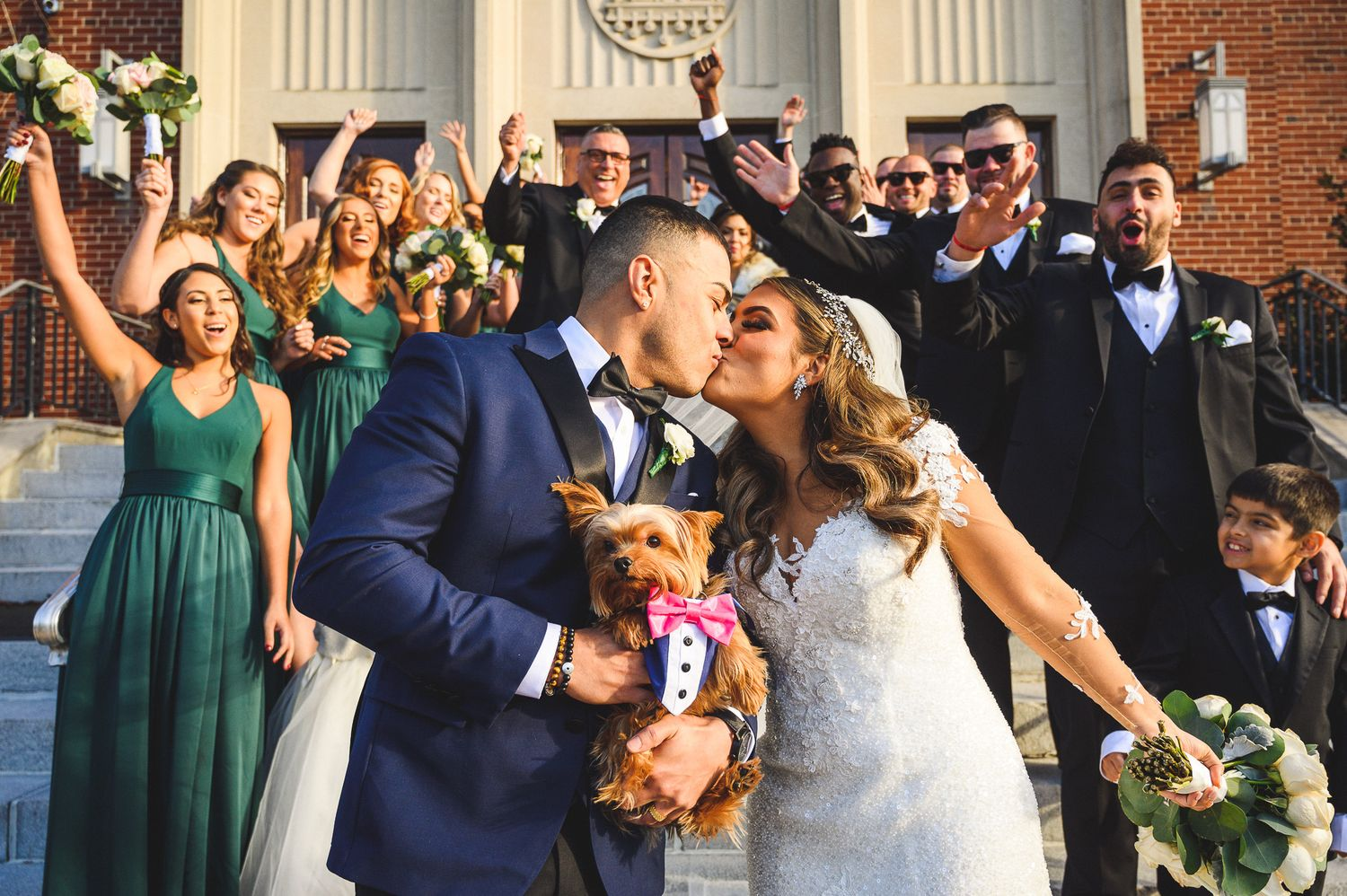 bride and groom kiss outside church with their dog