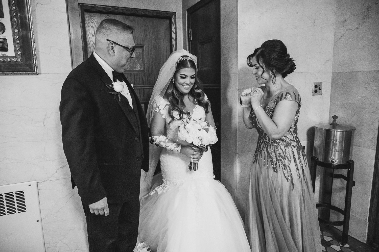 bride getting ready with mom and dad before walking down the isle