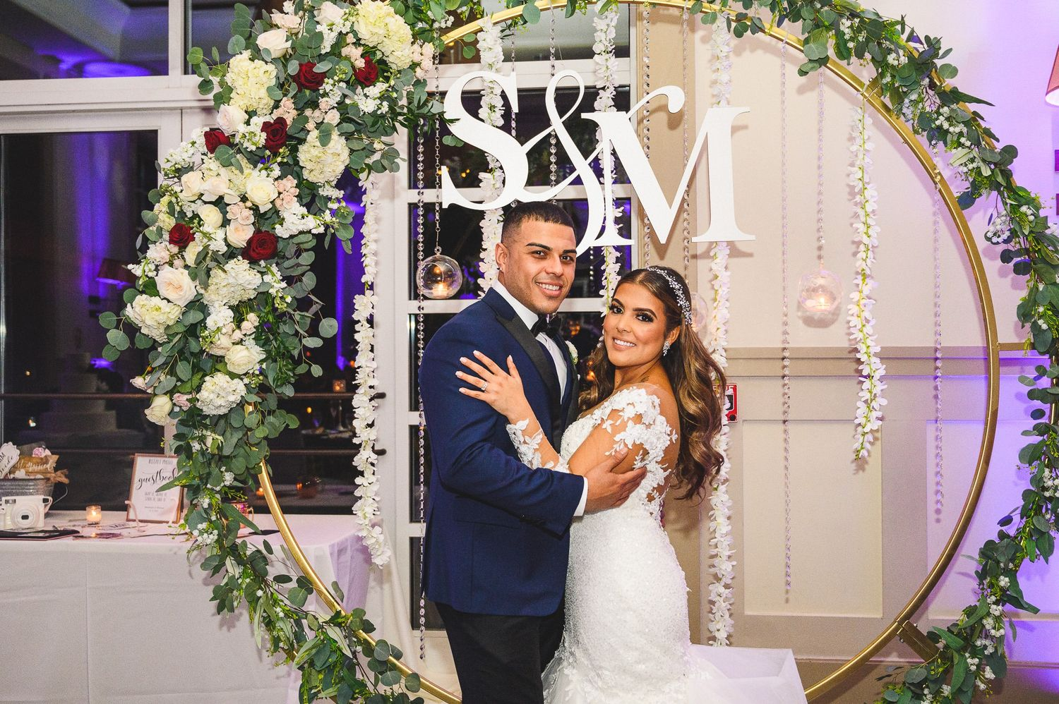 Bride and groom portrait in front flower arbor in reception