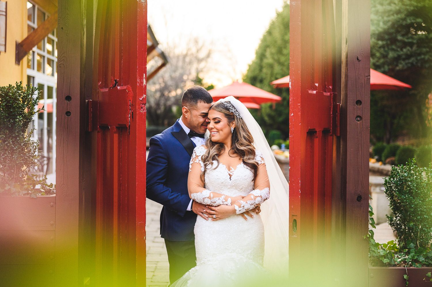 bride and groom portrait in between red doors at stone house